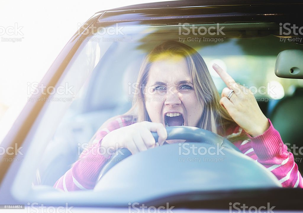 Enraged, frustrated woman  driver makes obscene gesture through windscreen, yelling stock photo