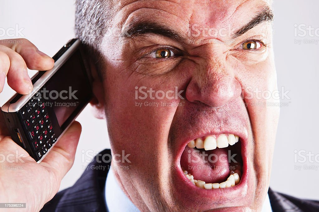 Enraged red-faced businessman yells into mobile phone stock photo