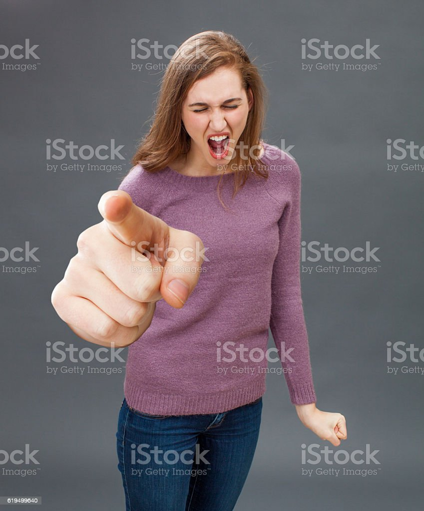 enraged young woman screaming, pointing a bossy over sized finger stock photo