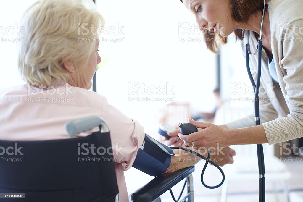 Ensuring her patient's blood pressure is normal royalty-free stock photo