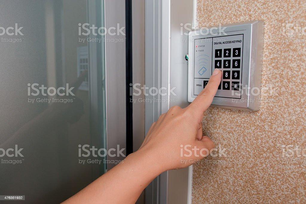 Entering security code keypad for opening the onlock door stock photo