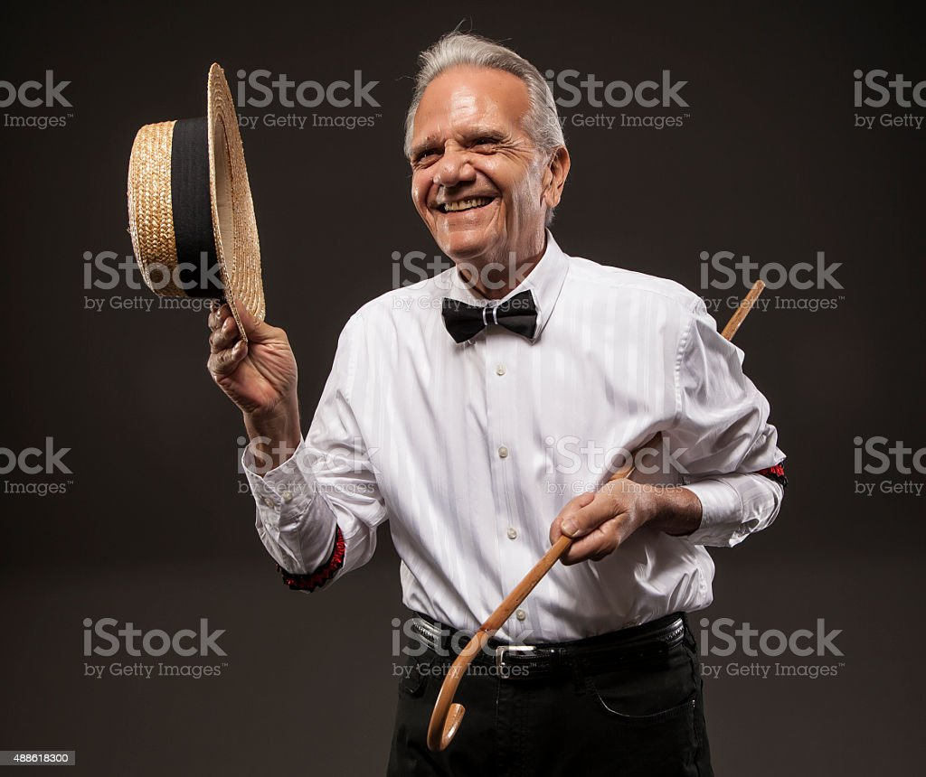 Entertainer with a hat and cane, smiling. stock photo