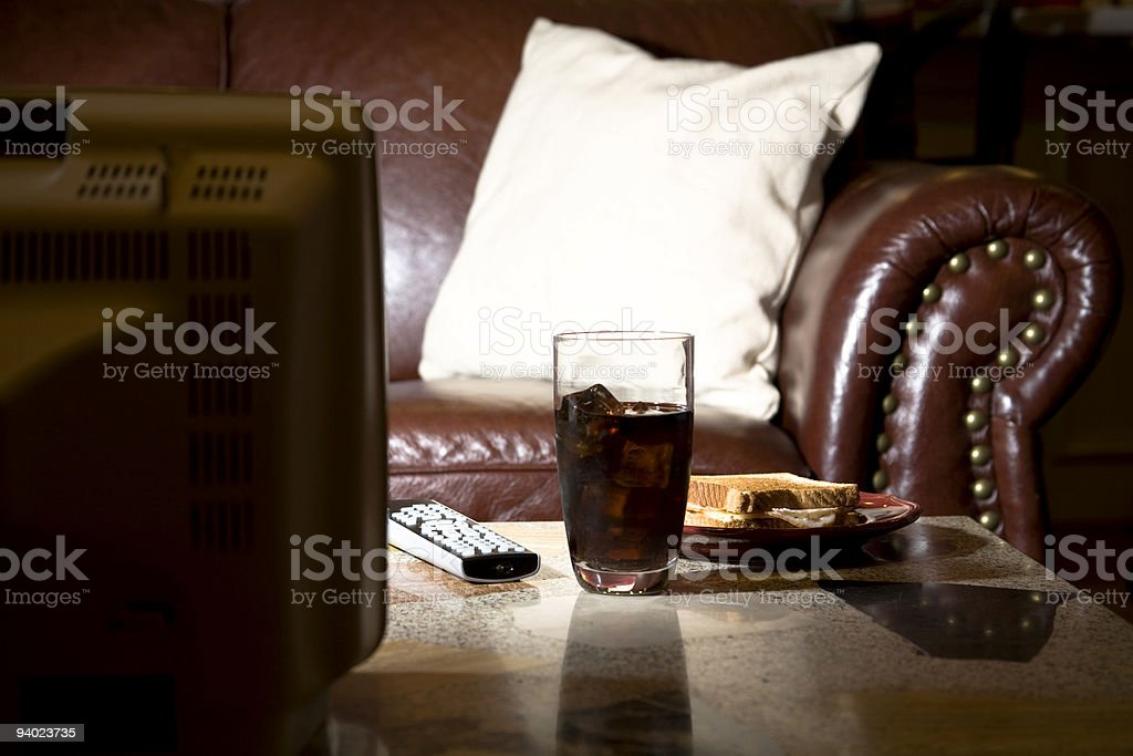Entertainment:  Coke and sandwich snack on table in front  television stock photo