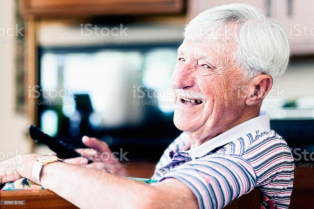 Enthusiastic 90-year-old man choosing TV channel looks round smiling stock photo