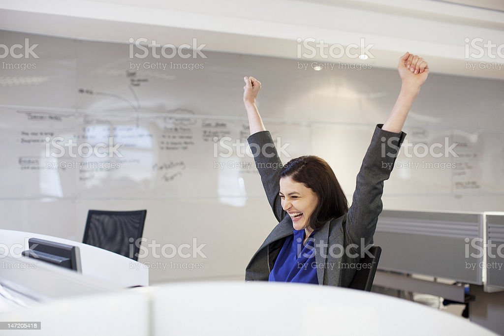 Enthusiastic businesswoman with arms raised in office stock photo