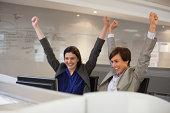 Enthusiastic businesswomen with arms raised in office