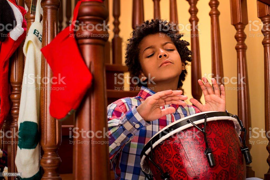 Enthusiastic darkskinned boy playing drum. stock photo