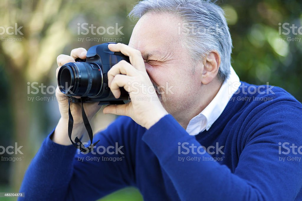 Enthusiastic photographer taking a photo outdoor. royalty-free stock photo