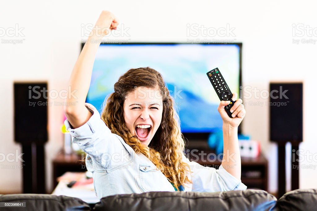 Enthusiastic young female spectator turns from TV cheering triumphantly stock photo