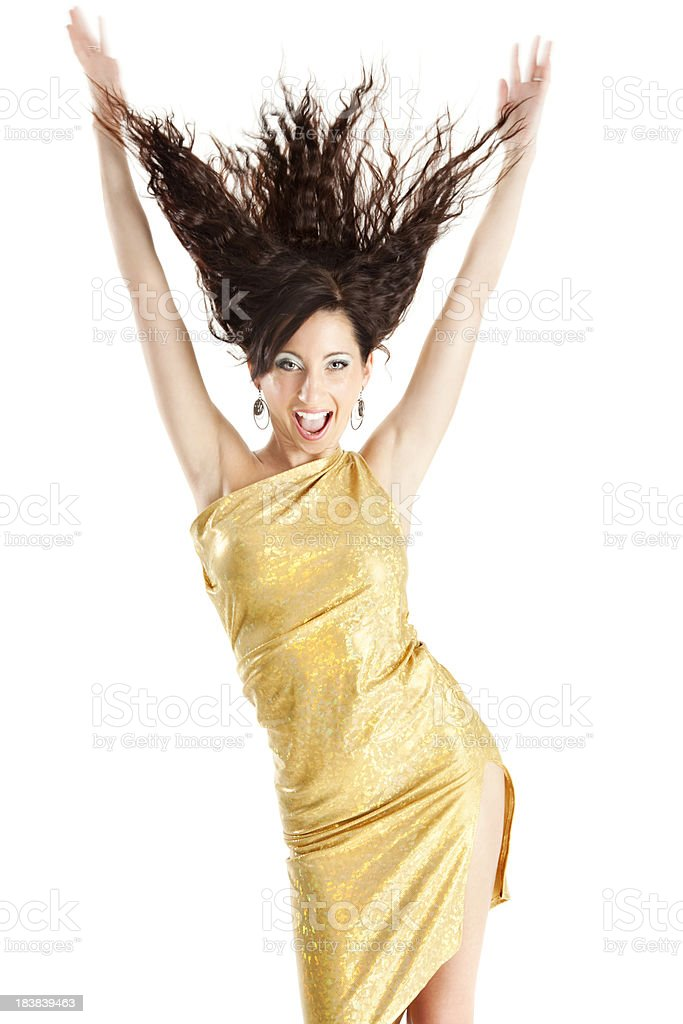 Enthusiastic Young Woman in Gold Dress Flipping Hair stock photo