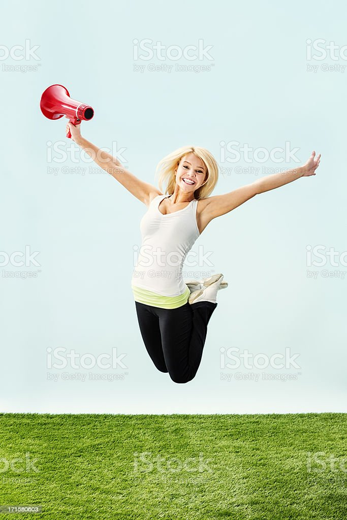 Enthusiastic Young Woman Jumping with Red Megaphone royalty-free stock photo