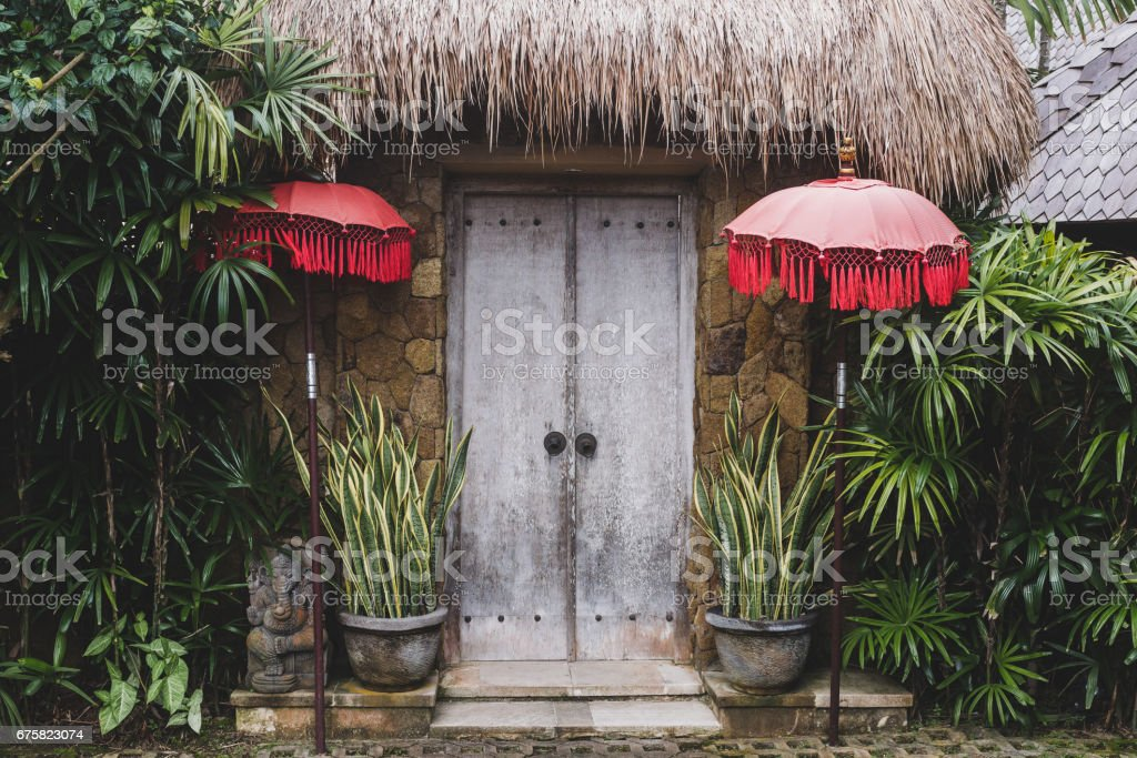Entrance in traditional bali house with wooden door, straw roof and red umbrellas stock photo
