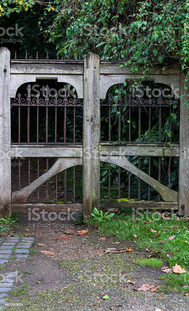 Entrance of a graveyard with a closed wooden gate stock photo