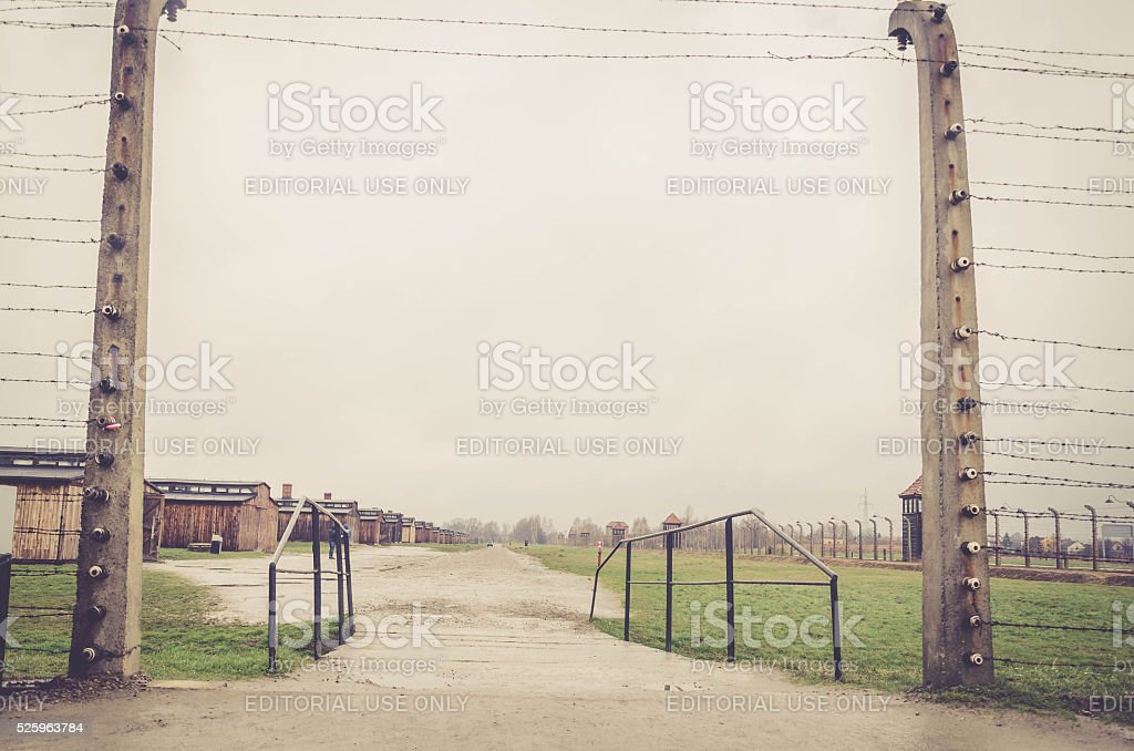 Entrance through electrical fence that surrounds the camp Auschwitz stock photo