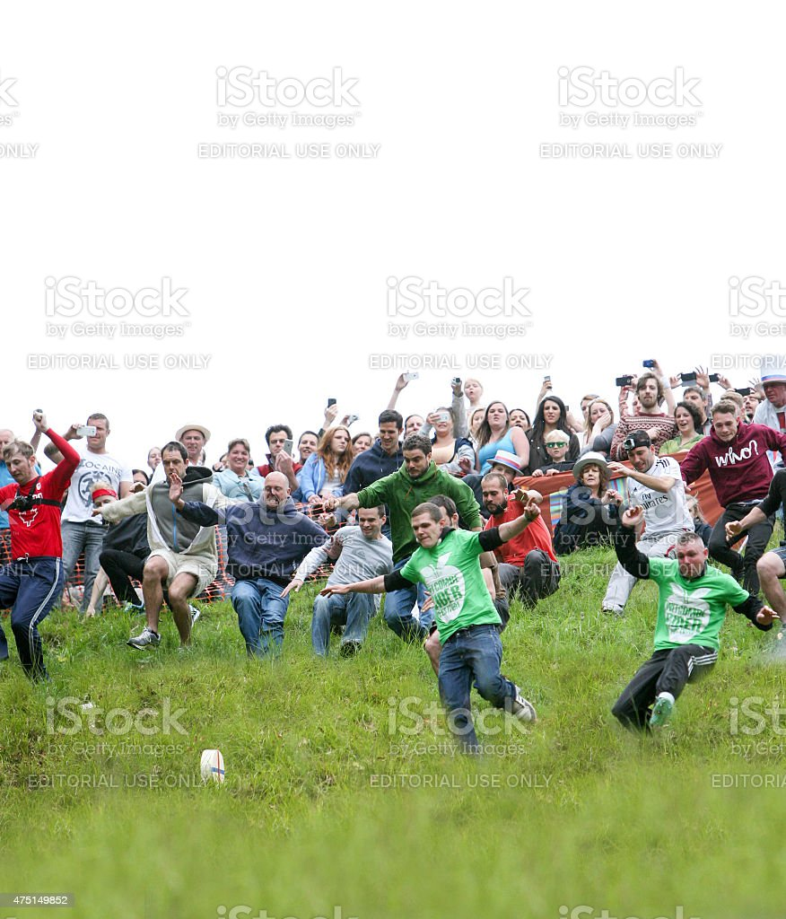 Entrants chasing the cheese at the 2015 'Cheese Rolling' stock photo