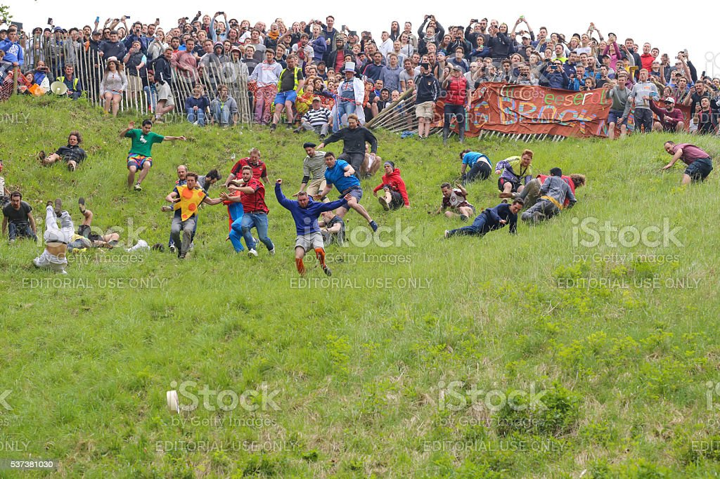 Entrants chasing the cheese at the 2016 'Cheese Rolling' stock photo