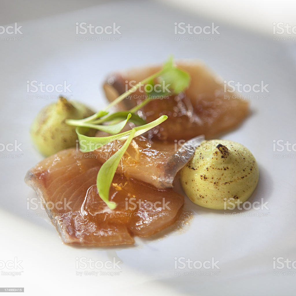 Entree of kingfish sashimi with dashi jelly and micro herbs royalty-free stock photo
