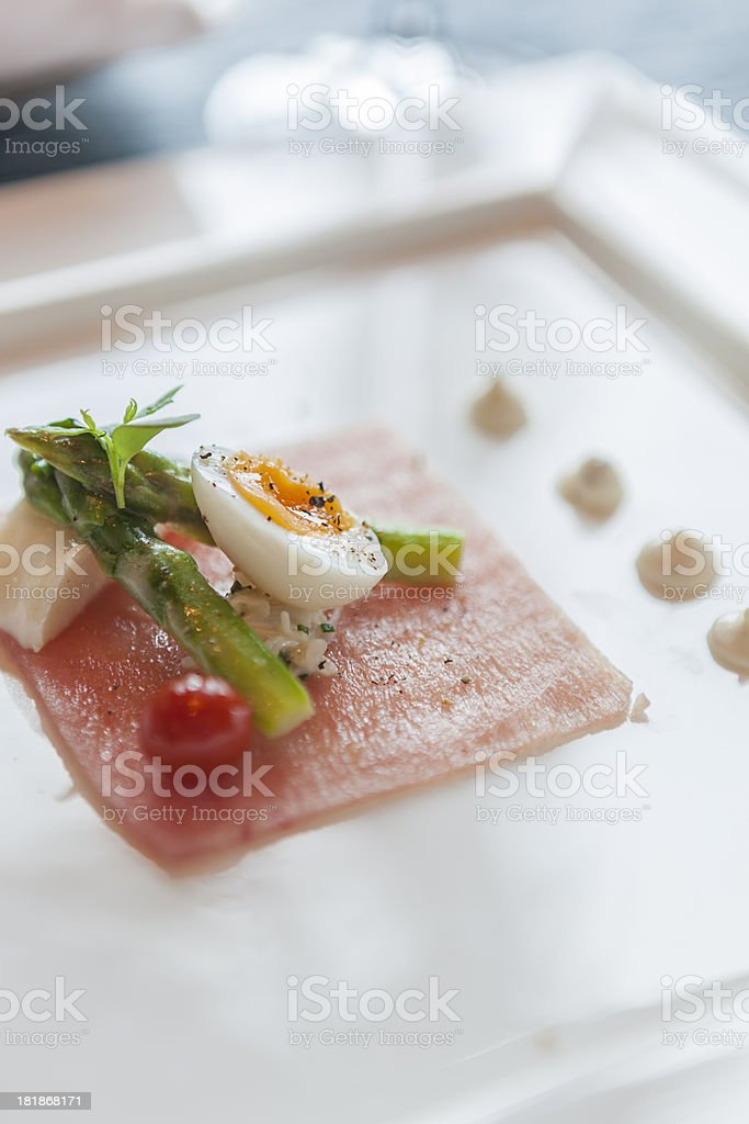 Entree of salmon carpaccio with baby asparagus and quail egg royalty-free stock photo