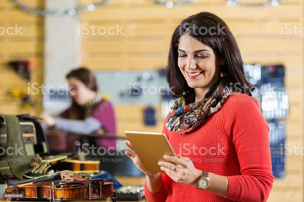 Entrepreneur checking customer orders in small local music shop stock photo