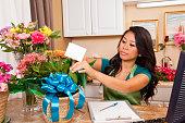 Entrepreneur florist preparing flower arrangements in shop.