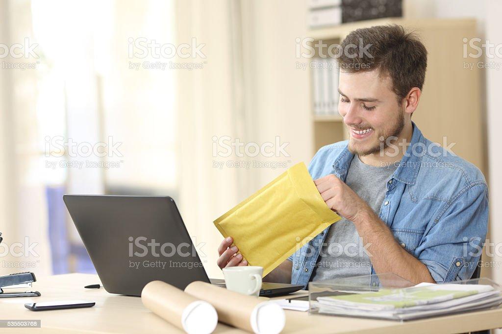 Entrepreneur opening a padded envelope stock photo