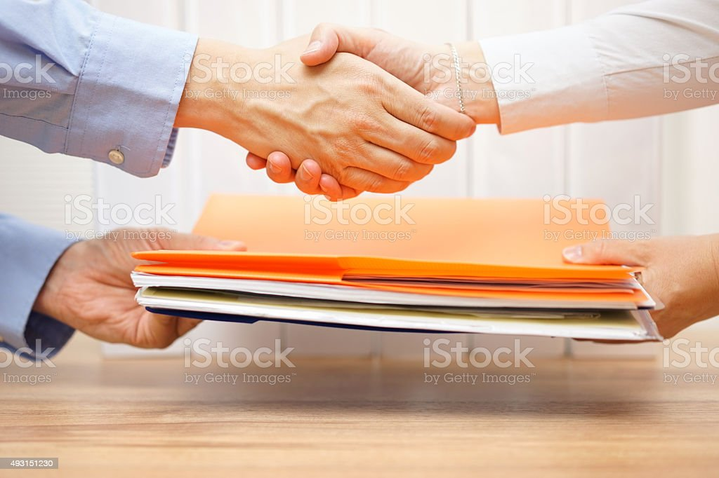 entrepreneur shaking hands with his accountant after passing documentation stock photo