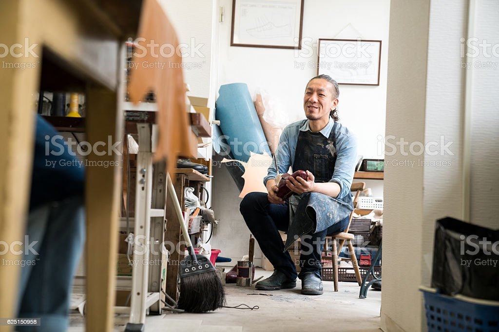 Entrepreneur shoemaker working in his small shoe shop stock photo