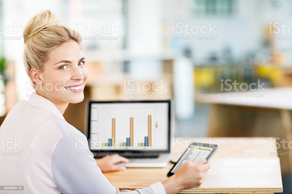 Entrepreneur Using Digital Tablet And Laptop At Desk In Office stock photo