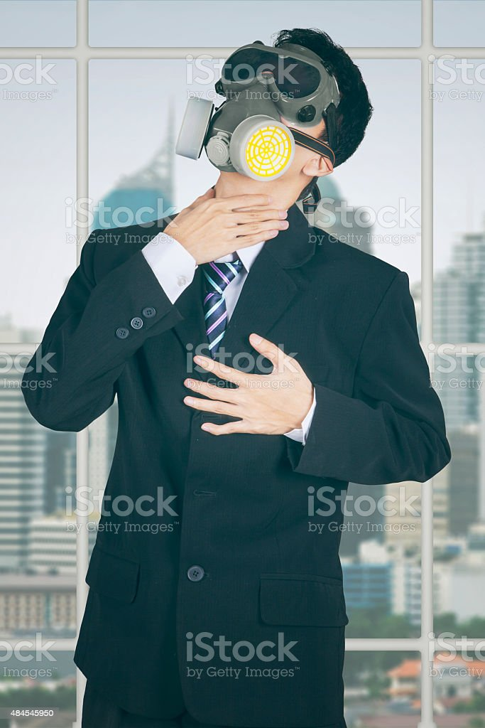 Entrepreneur with gas mask in the office stock photo