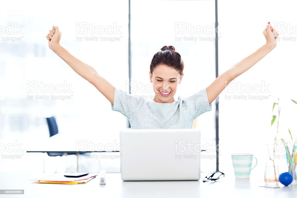 Entrepreneur With Laptop Celebrating Success At Desk stock photo