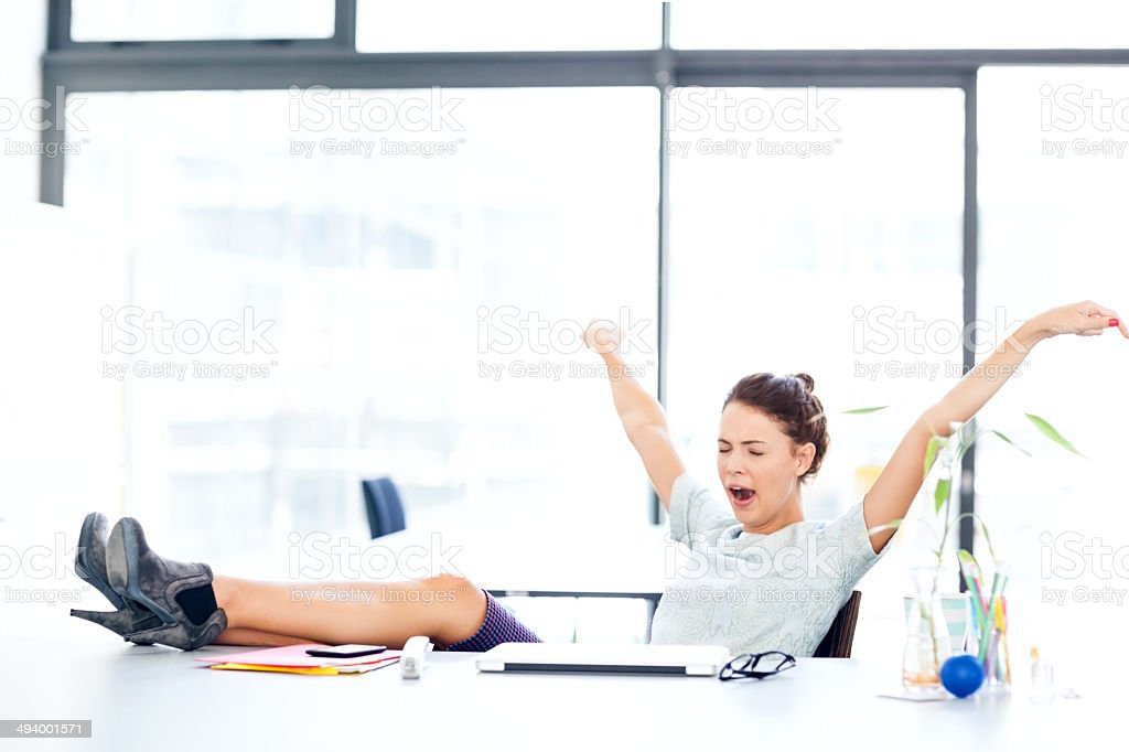 Entrepreneur Yawning While Stretching At Office Desk stock photo