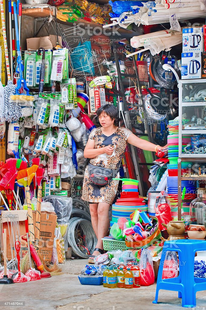 Entrepreneurial Woman in front of fully leoaded shop, Kunming, China. stock photo