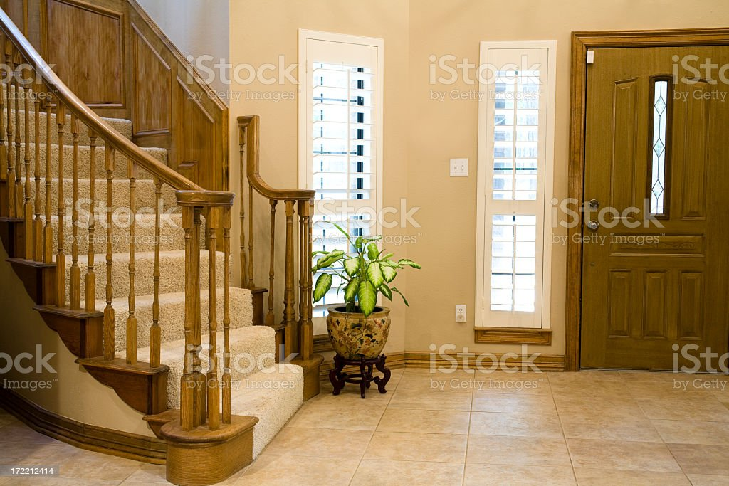 Entry Hall of upscale, modern home. Stairway, front door, foyer. stock photo