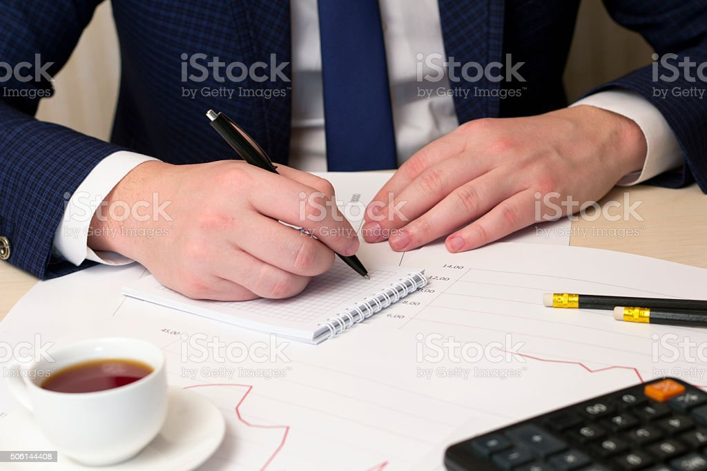 entry in the notebook black pen and coffee, calculator stock photo