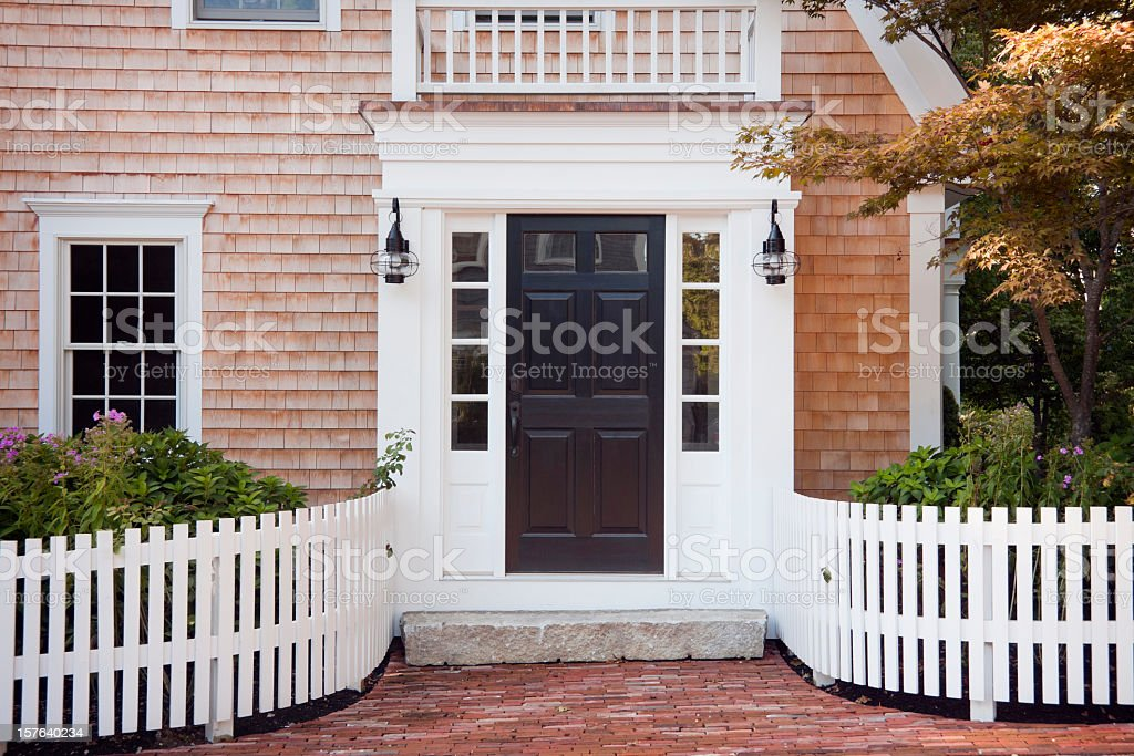 Entryway of brick New England home with picket fence stock photo