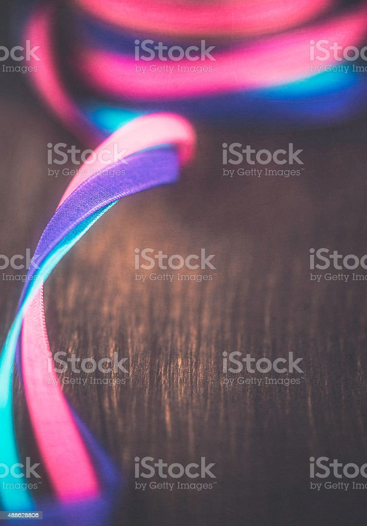 Entwined ribbons on rustic table stock photo
