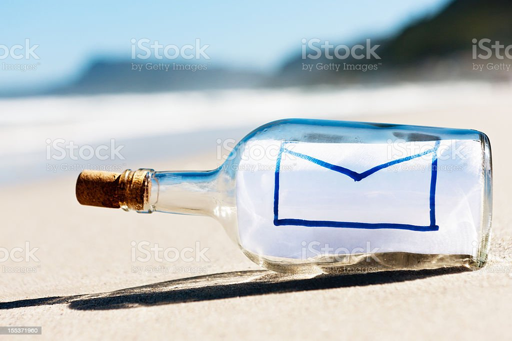 Envelope email icon is message in bottle on empty beach royalty-free stock photo
