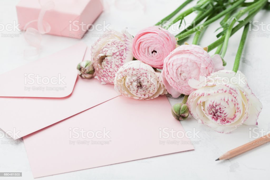 Envelope or letter, paper card, gift and pink ranunculus flowers on...