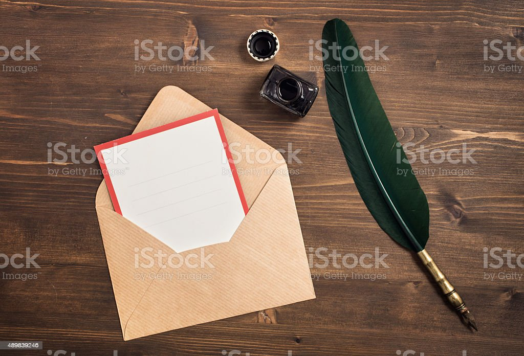 Envelope with empty card and quill pen on wooden table stock photo