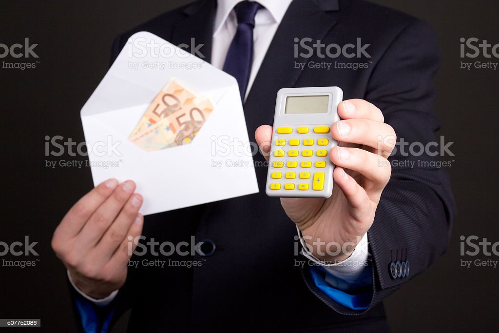envelope with money and calculator in business man hands stock photo