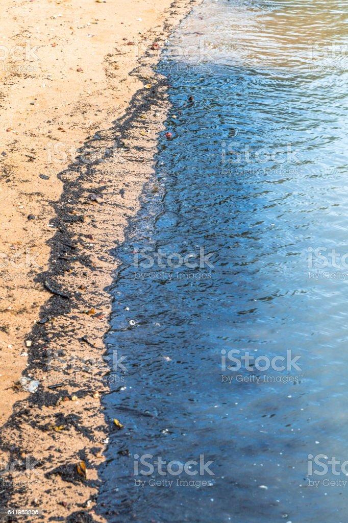 Environmental Disaster strikes when an oil spill causes pollution on a beach in the tropical paradise of Koh Lanta, Krabi, Thailand. stock photo