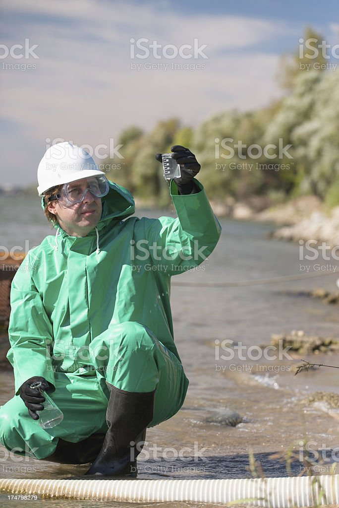 Environmentalist looking at sample of polluted water royalty-free stock photo