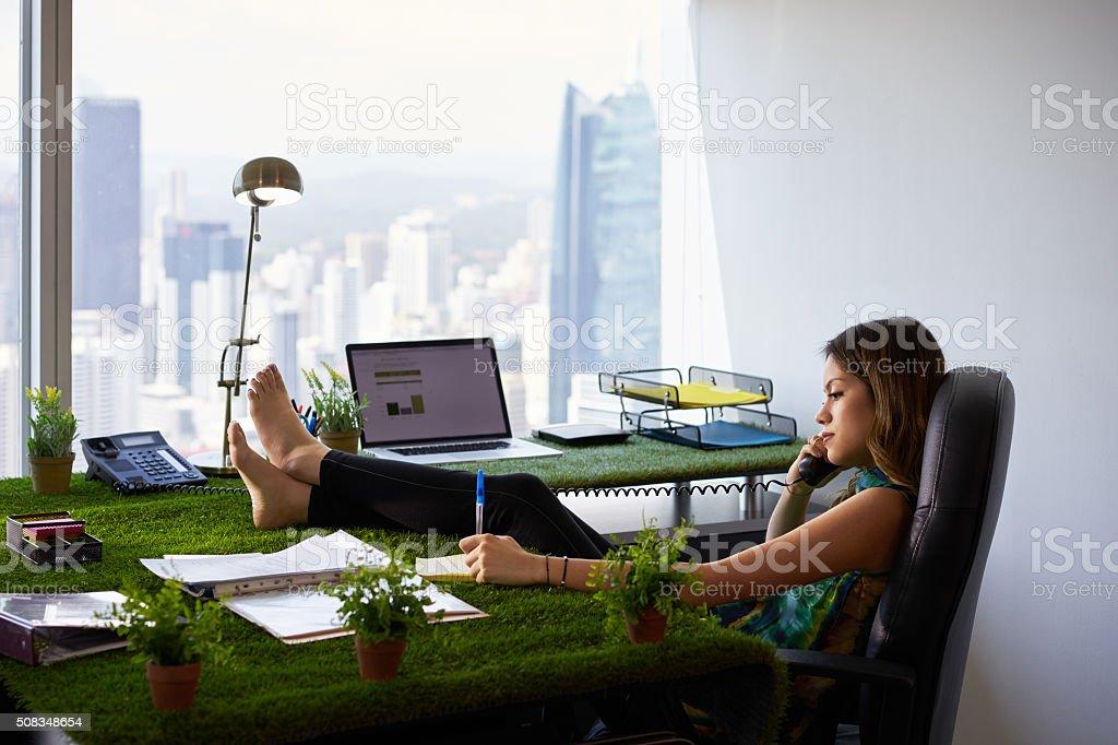 Environmentalist Woman Writes Note Barefeet On Office Desk stock photo