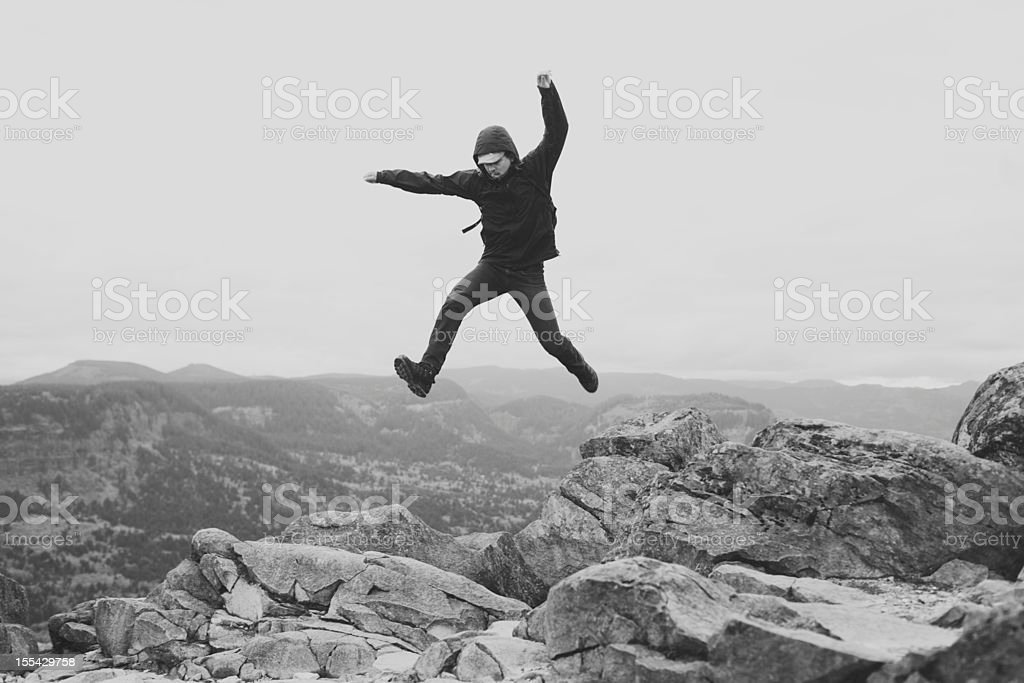 Epic Man Jumping Over Rocks stock photo