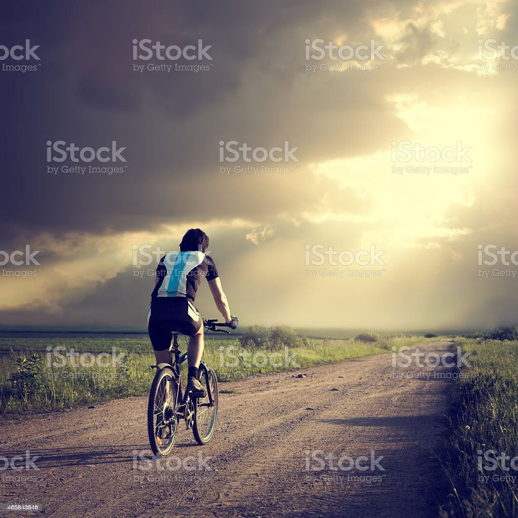 Epic Photo of Cyclist on Dramatic Sky Background stock photo