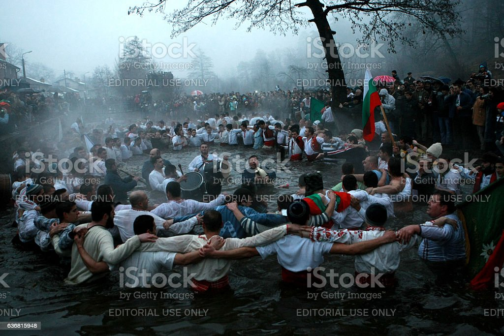 Epiphany Traditions - Jordan. Men dance in the icy waters stock photo
