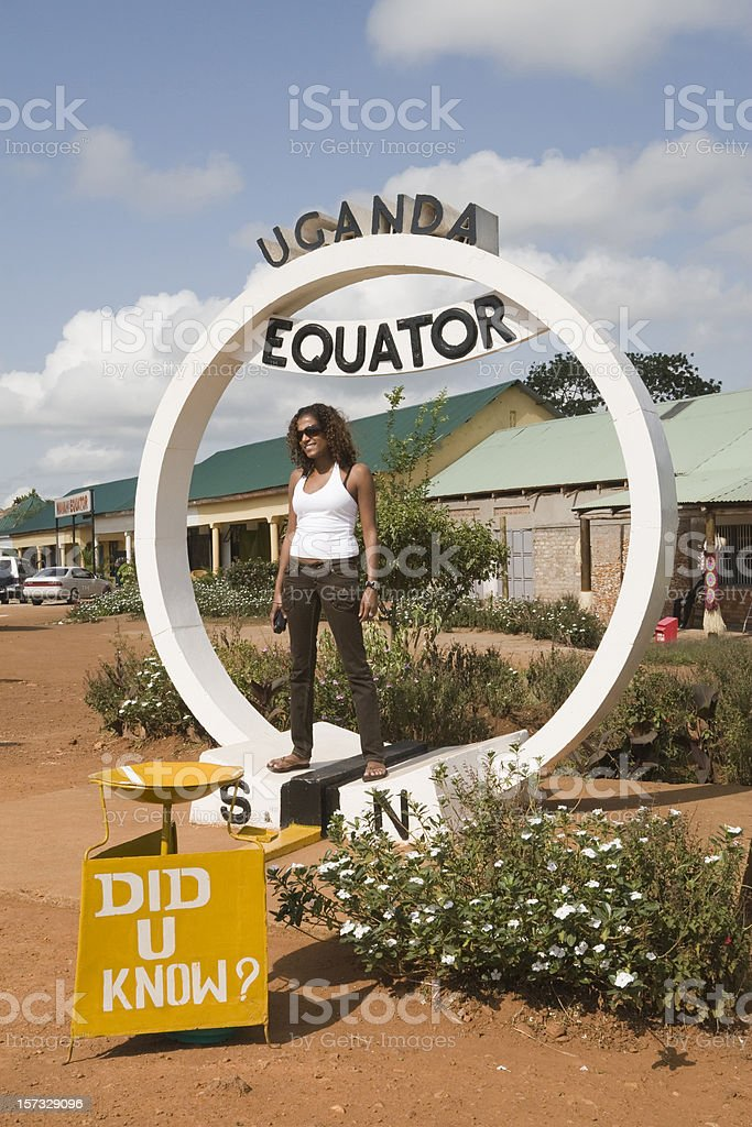 Equator in Uganda with young woman stock photo