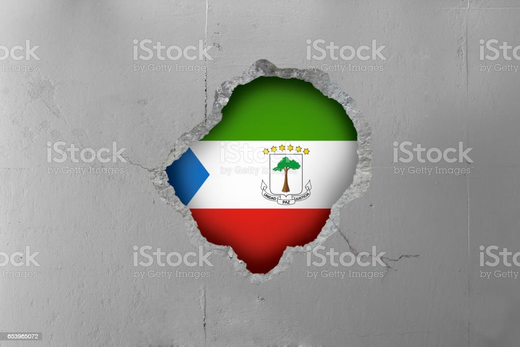 Equatorial Guinea's flag behind a concrete wall. stock photo