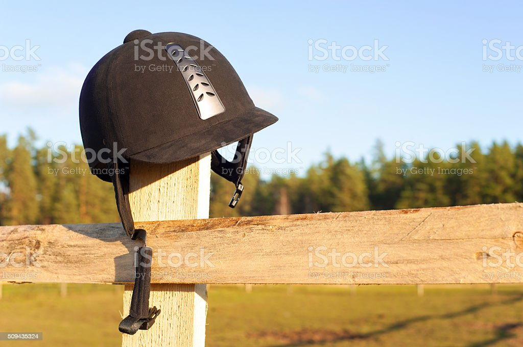 Equestrian helmet forgotten hanging on the wooden fence. stock photo