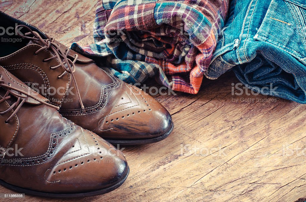 Equipment, apparel, jeans, shirts, shoes on the wooden floor. stock photo